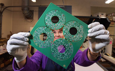 Judy Ortiz Rizek holds a printed circuit board